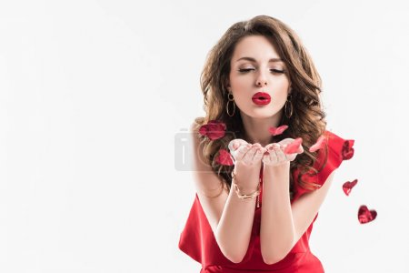 fashionable girl blowing on heart shaped confetti isolated on white, valentines day concept