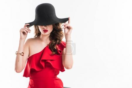 attractive fashionable girl hiding eyes under black hat isolated on white