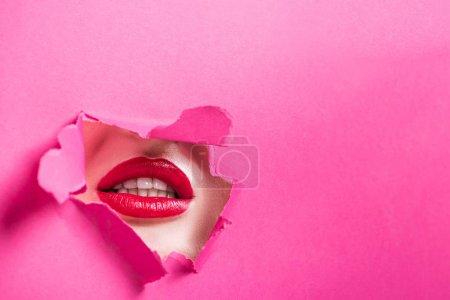 Photo pour Image recadrée de fille séduisante montrant les lèvres dans le trou dans du papier rose - image libre de droit