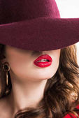 sexy woman with red lips hiding eyes under burgundy hat