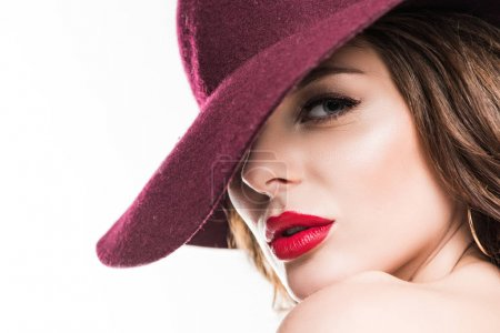 headshot of attractive girl in burgundy hat looking at camera isolated on white