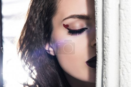 cropped image of girl with painted heart on eyelid standing with closed eyes behind column, valentines day concept