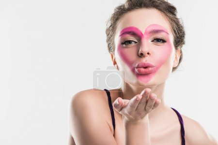 girl with painted pink heart on face sending air kiss isolated on white, valentines day concept