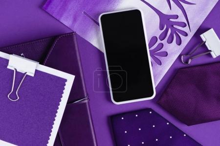 Photo pour Vue de dessus de l'espace de travail dans les nuances de couleur pourpre avec smartpohone et fournitures - image libre de droit
