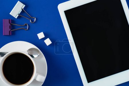 top view of workspace with tablet and coffee cup