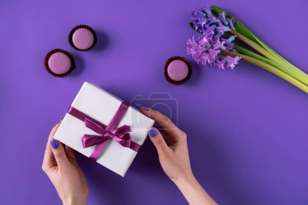 cropped image of girl holding present box on purple