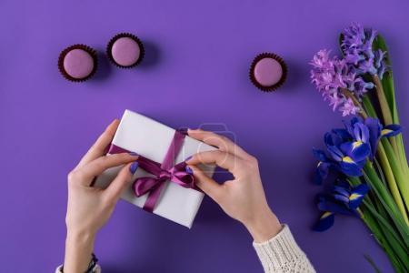 Photo for Cropped image of girl opening present box on purple - Royalty Free Image