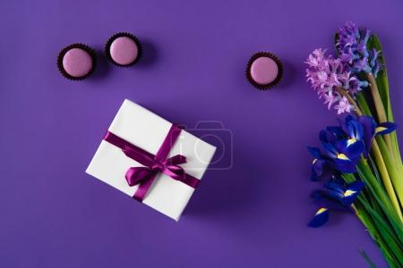 top view of present box and yummy macarons on purple