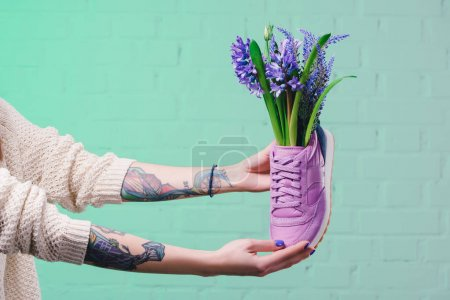 cropped image of girl holding shoe with hyacinth flowers