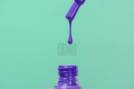 nail polish pouring down into bottle isolated on turquoise