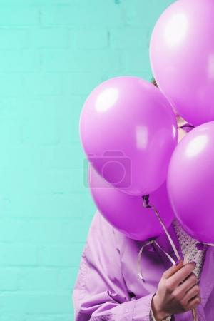 young woman in coat hiding behind pink helium balloons