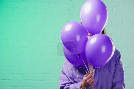 young woman in coat hiding behind purple helium balloons