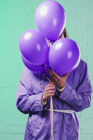 mujer joven en abrigo escondido detrás de globos púrpura