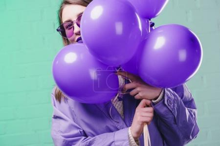 young woman in sunglasses hiding behind purple balloons