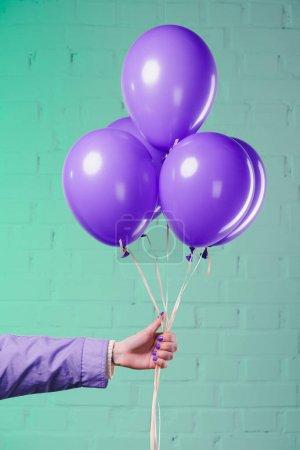 tiro recortado de mujer sosteniendo globos de helio púrpura