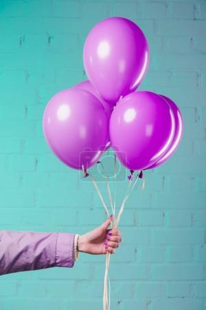 tiro recortado de mujer sosteniendo globos de helio rosa