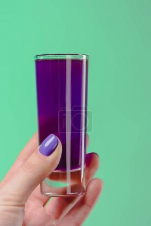 cropped image of woman holding glass with purple cocktail isolated on turquoise