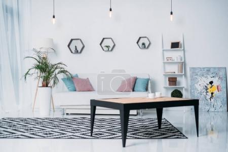 Photo for Wooden table and sofa with pillows in room - Royalty Free Image