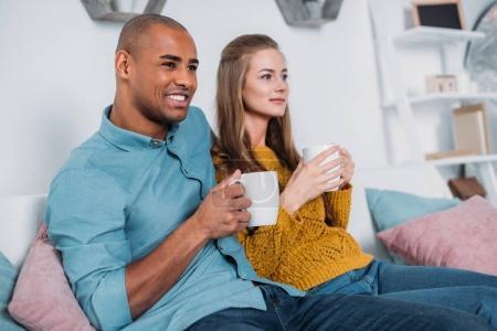 Multicultural couple assis sur le canapé avec du café et à la recherche.