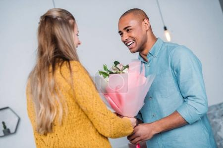 smiling african american boyfriend presenting bouquet to girlfriend