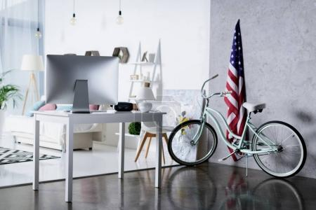 silver computer on table and bicycle near wall in room