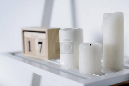 Photo pour Trois bougies blanches sur étagère blanche - image libre de droit