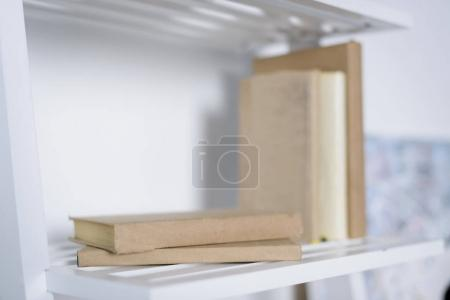 books on white shelves in light apartment