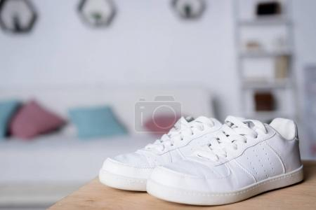 pair of new white shoes on wooden table in room