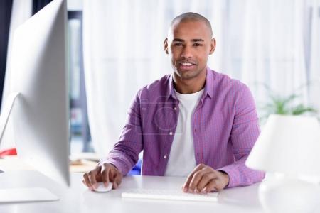 sonriente afroamericano hombre sentado en el ordenador y mirando a la cámara