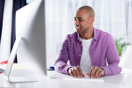 smiling african american man typing at keyboard