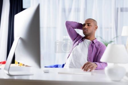 tired african american man looking at computer at home