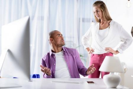 caucasian girlfriend looking skeptically at african american boyfriend at computer