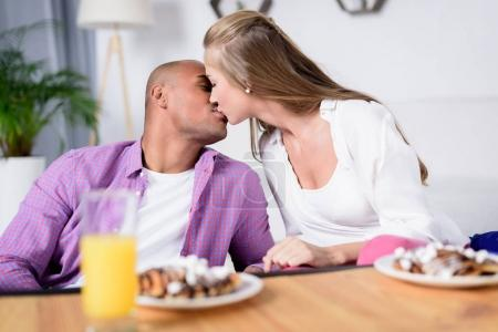 Photo for Multicultural couple kissing near table with food - Royalty Free Image