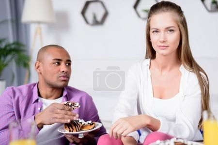 african american boyfriend holding cookies and looking at caucasian girlfriend