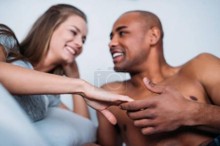 smiling multicultural couple holding hands in bed