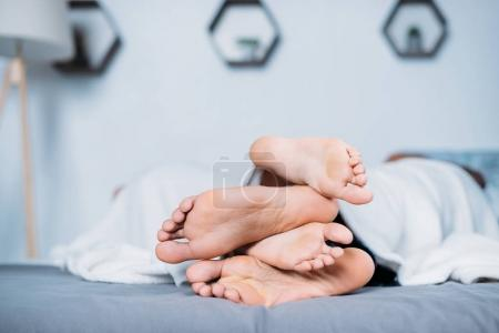 multicultural couple lying under blanket in bed