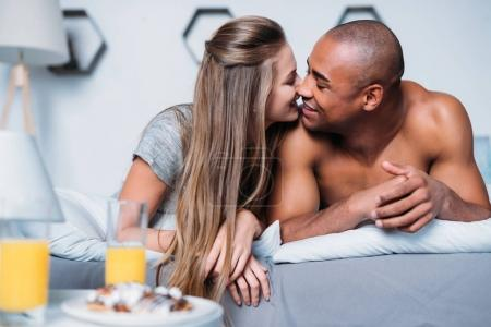 Photo for Multicultural couple kissing and lying on bed - Royalty Free Image