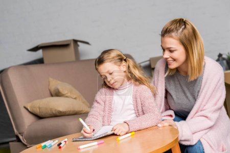 Photo for Happy mother looking at daughter drawing with felt tip pens at table - Royalty Free Image