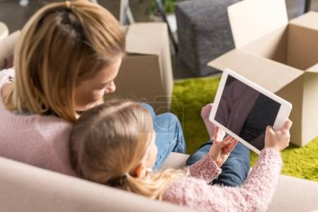 Photo for Mother and daughter using digital tablet with blank screen while moving home - Royalty Free Image