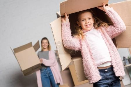 happy mother and daughter holding cardboard boxes while moving home