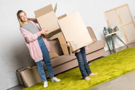 Photo for Happy mother and little daughter holding cardboard boxes while moving home - Royalty Free Image