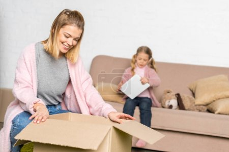 smiling woman packing cardboard box while little daughter using digital tablet