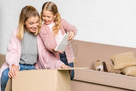 happy mother and daughter with digital tablet packing cardboard box during relocation