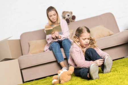 child wearing shoes on carpet while mother reading book on sofa