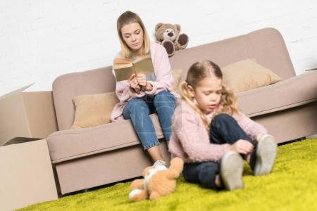 kid playing with teddy bear on carpet while mother reading book on sofa