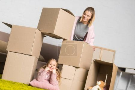 mother and daughter having fun with cardboard boxes while moving home