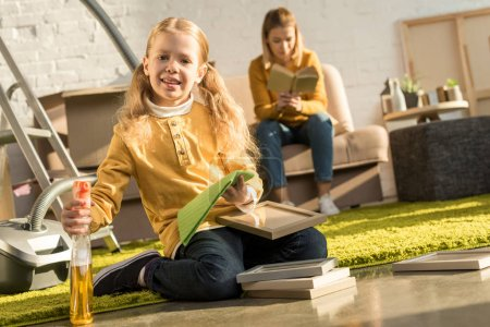 Photo for Cute little child cleaning frames and smiling at camera while mother reading book after relocation - Royalty Free Image