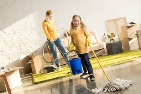 mother and daughter with mop and vacuum cleaner cleaning room while moving home