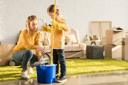 Photo for Mother and daughter cleaning apartment with mop after relocation - Royalty Free Image