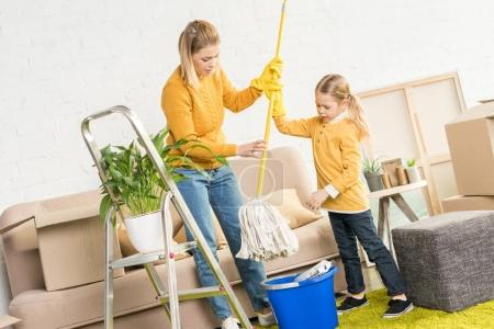 Photo for Mother and daughter holding mop and cleaning room after relocation - Royalty Free Image